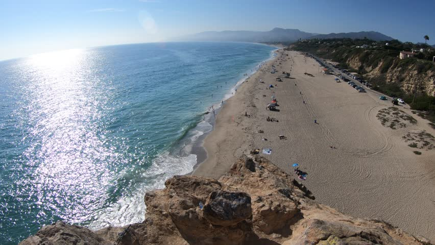 Aerial view of panoramic Point Dume State Beach from Point Dume promontory on Malibu coast, Pacific Ocean in CA, United States. California West Coast. Blue sky, summer season in sunny day.