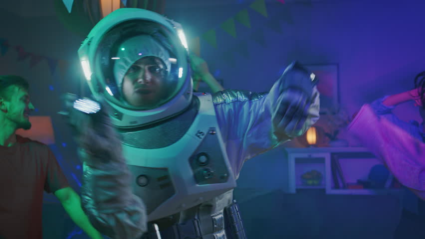 At the College House Costume Party: Fun Guy Wearing Space Suit Dances Off, Doing Groovy Funky Robot Dance Modern Moves. With Him Beautiful Girls and Boys Dancing in Neon Lights. | Shutterstock HD Video #1020544102
