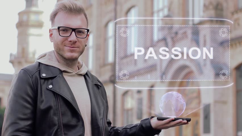 Smart young man with glasses shows a conceptual hologram Passion. Student in casual clothes with future technology mobile screen on university background