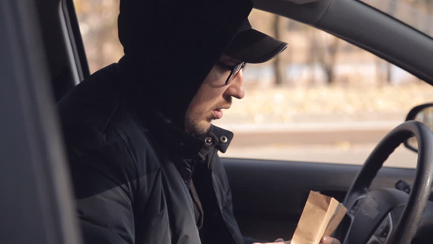 A private detective or a spy conducts surveillance of the object of surveillance. A man secretly taking pictures from the car window | Shutterstock HD Video #1020566692