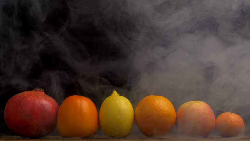 Tropical juicy fruits pomegranate, orange, tangerine, lemon and persimmon on a black background, from which blows freshness and evaporation, smoke, 4K   Shutterstock HD Video #1020574042