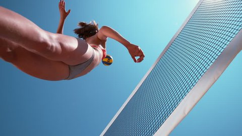 SLOW MOTION, BOTTOM UP, CLOSE UP: Young Caucasian woman playing volleyball spikes the ball over the net under the clear blue sky. Awesome shot of athletic girl jumping in the air to score a point.