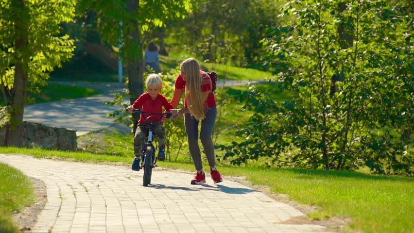 Slow motion shot of a young woman teach her little son how to ride a bicycle