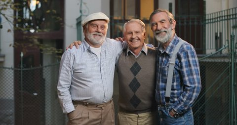 Portrait of the three Caucasian old men standing, hugging and smiling to the camera in front of the camera at the house. Outdoor.