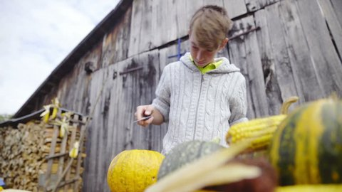 Young boy cleaning pumpking inside low angle HD. Slide low angle shot of boy on table removing inside meat and seeds of big pumpkin. Old wooden retro background.