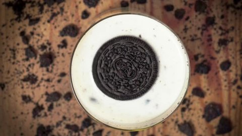 Oreo cookie with crumbs in the glass of milk. Editorial