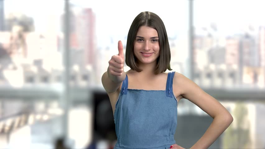 Cute woman gesturing thumb up. Beautiful young lady smiling and showing with fingers ok sign. Symbol of peace. | Shutterstock HD Video #1020677122