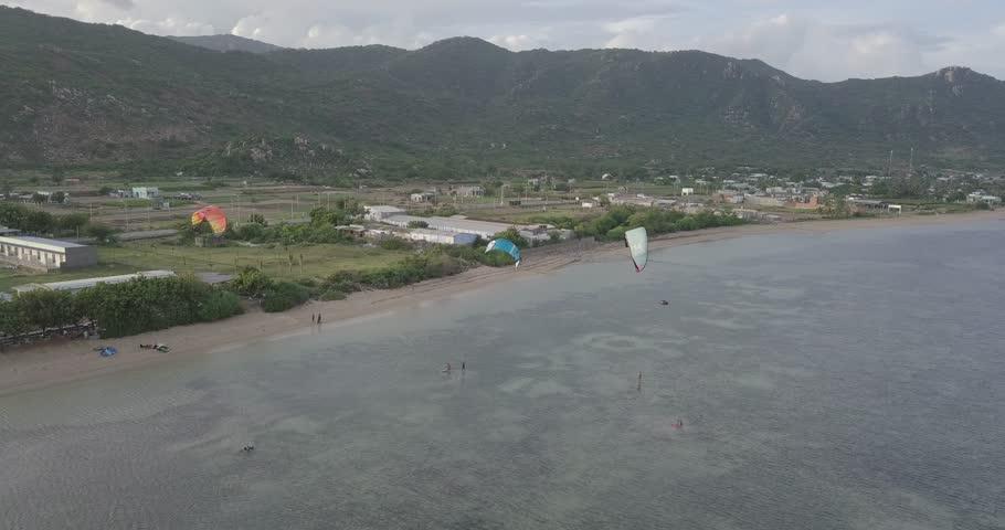 Extreme sport kitesurfing in tropical blue ocean, clear beach. Aerial  | Shutterstock HD Video #1020707032