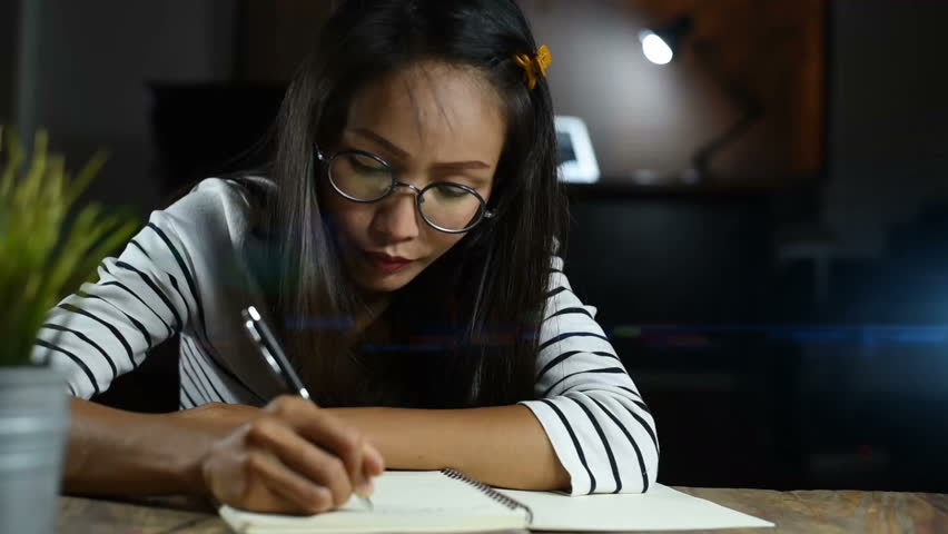 Asian woman writing down on a white blank notebook on table | Shutterstock HD Video #1020746362