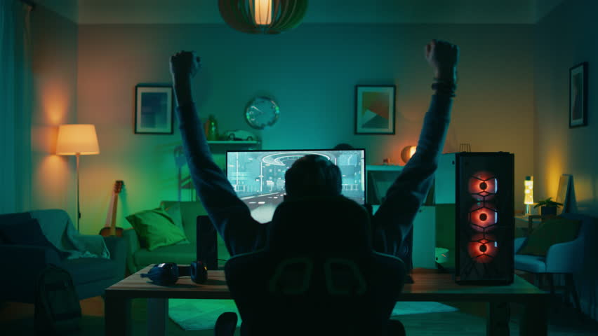 Back Shot of a Gamer Playing and Winning in First-Person Shooter Online Video Game on His Powerful Personal Computer. Room and PC have Colorful Neon Led Lights. Cozy Evening at Home. | Shutterstock HD Video #1020758392