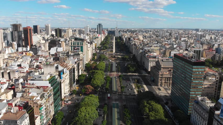 Panoramic Aerial drone view of Buenos Aires obelisk on avenida de Julio in Buenos Aires, Argentina. Shows buildings and skyscrapers with car traffic in the Street below. #1020766822