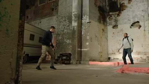 Two men wrestle in front of an abandoned camper trailer in an old warehouse in moody lighting. Wide shot in 4K with an Alexa Mini camera
