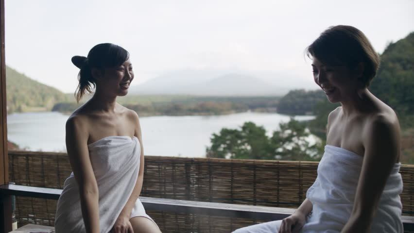 Two relaxed Japanese women sitting on the edge of a hot water bath and looking out to Mount Fuji in the background with soft natural lighting. Medium shot on 4k RED camera.