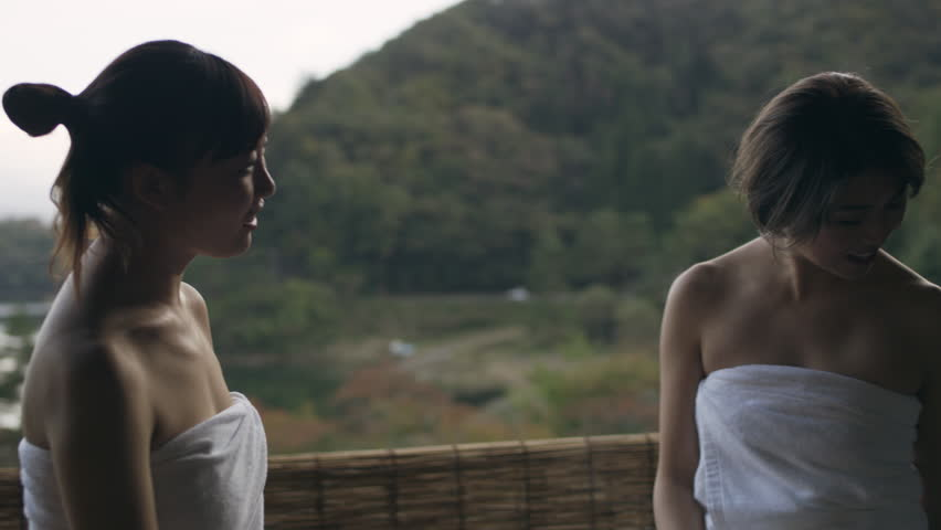 Medium shot on 4k RED camera. Two Japanese women sitting with their legs in a hot water bath and talking happily in a traditional spa with soft natural lighting. | Shutterstock HD Video #1020784102