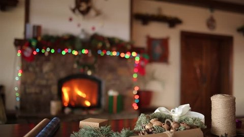 Bearded man sitting and tying a bow on a gifts for New Year near fireplace. Guy wearing Christmas hat wrapping present boxes in paper adding fir branches, cones, cane candies. Clip pack sequence.