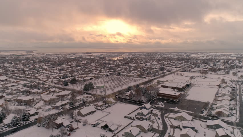Aerial view flying over snow covered town towards the sunset on cold winter evening. | Shutterstock HD Video #1020787402
