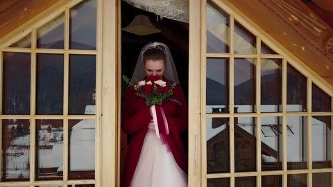 Drone camera flies away from beautiful bride standing on mezzanine of wooden chalet cottage revealing the mountain valley covered with spruce forest and snow. Fairy tale aerial from princess in castle
