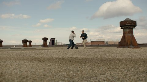 Two men fight with martial arts on a warehouse rooftop with skilled kicks and punches in overcast sunlight. Wideshot in 4K with an Alexa Mini camera