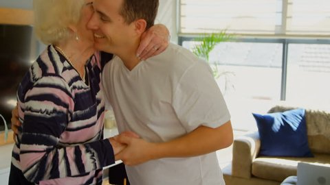 Caucasian adult son kissing his elder retired mother. Family standing dancing in living room at home.