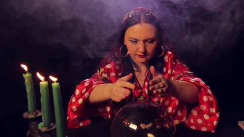 A gypsy fortune teller at the table reads the future in a magic ball.