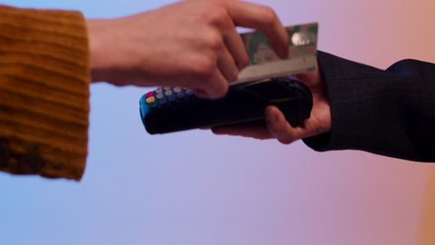 Payment with magnetic stripe credit card through the terminal, isolated on blue and yellow background. Stock. Close up for woman paying by chipless card through credit card machine.