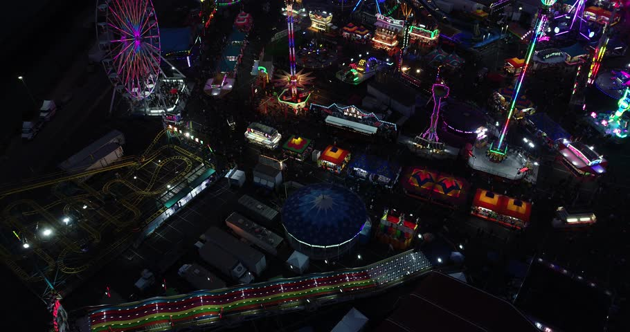 Aerial of fair/carnival. slowly dollies forward to reveal carnival rides and lights at night. | Shutterstock HD Video #1020847942