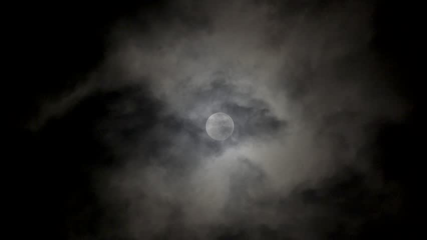 Full moon on dark cloudy night. Clouds passing by the moon in spooky feeling like thriller and horror films. Werewolf moon, dark night sky, black clouds, full moon clouds, ghost, horror films.