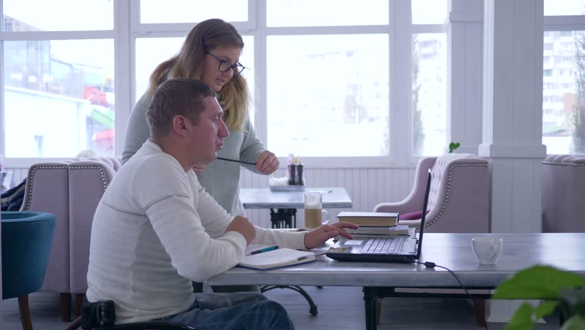Tutoring for invalid, successful senior crippled man in wheelchair with educator woman using smart computer technology during personal lesson in cafe | Shutterstock HD Video #1020863092