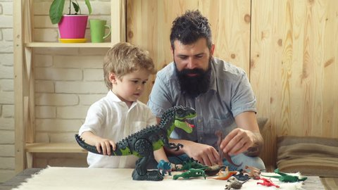 Father and son play with dinosaurs. Adorable little child plays with his bearded father with plastic dinosaurs. Father and cute little son playing toy dinosaurs on tabletop together at home