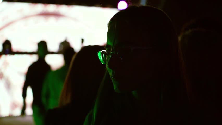 Fashionable young woman with glasses dances at nightclub with disco lights   Shutterstock HD Video #1020886882