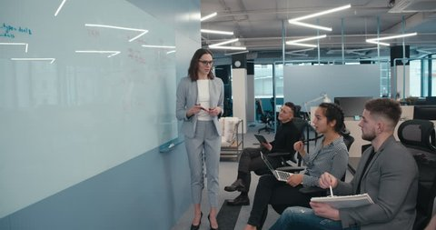 Attractive mid-30s female manager leading creative brainstorming meeting in modern office, presenting her ideas to the team on white board. 4K UHD