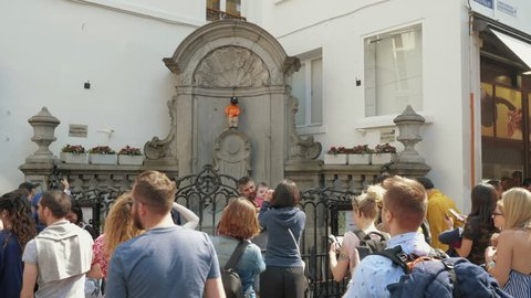 Brussels, Belgium - 21.04.2018: Tourist making photo of Manneken Pis or Pissing Boy statue in Brussels. Statue is one of main touristic attraction and landmark of Brussel.