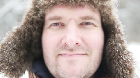 Big Russian man on the street in winter. He is in a huge warm hat, not shaved, with a smirk on his face. Then the guy smiles. Slow shooting, snow falls on his face from the sky