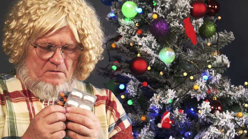 Happy elderly man with gray beards takes medicine and drinks tablets with water on background of Christmas tree in garlands, green UFO balls, proton purple toys, plastic pink angel, neon glow   Shutterstock HD Video #1020971842