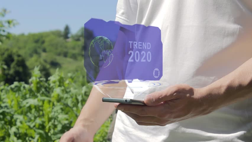 Man shows concept hologram Trend 2020 on his phone. Person in white t-shirt with future technology holographic screen and green nature background | Shutterstock HD Video #1021015072