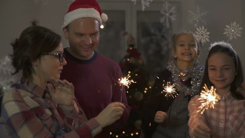 Sparklers - dad, mom and little daughters with bengal lights together congratulates new year, decorated Christmas tree, ornamental snowflakes, concept happy holidays and best wishes, slow motion.
