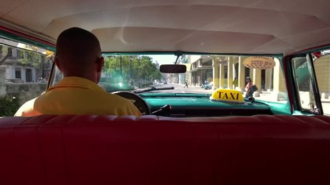 Cuban taxi driver in a classic 1950's american vintage car through old Havana, Cuba