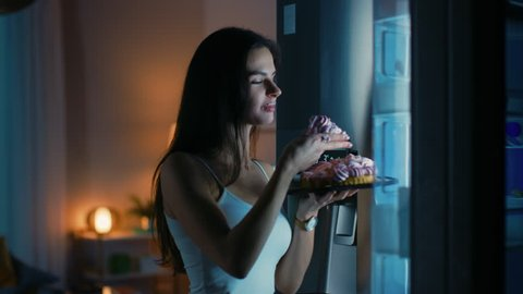 Beautiful Young Woman Comes to the Kitchen in the Evening. She is Hungry and Opens the Fridge. Takes out a Piece of a Delicious Creamy Cake and Bites It. She Feels Satisfied.