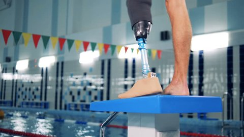 Close up of a male healthy leg and a prosthetic one in the swimming pool