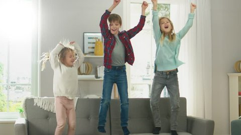 Two Cute Little Girls and Young Adorable Boy Have Fun, Jumping High on a Couch at Home. Happy Kids Dancing on a Sofa in the Sunny Living Room. In Slow Motion.