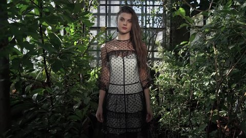 Fashion model with long brunette hair in a black and white dress is walking in a green botanical garden / pretty girl