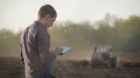 Farmer using digital tablet computer in cultivated field. Tractor in the background. Concept modern technology application in agricultural growing activity.