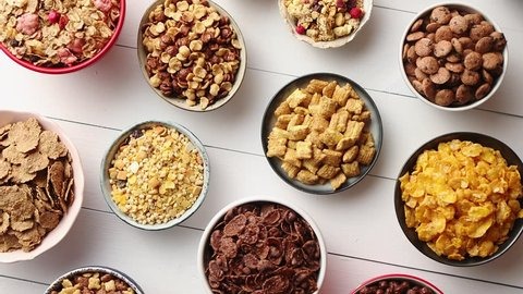 Assortment of different kinds cereals placed in ceramic bowls with cornflakes, granola, cereals and oatmeal. The concept of breakfast food. Flat lay, top view on white wooden table.