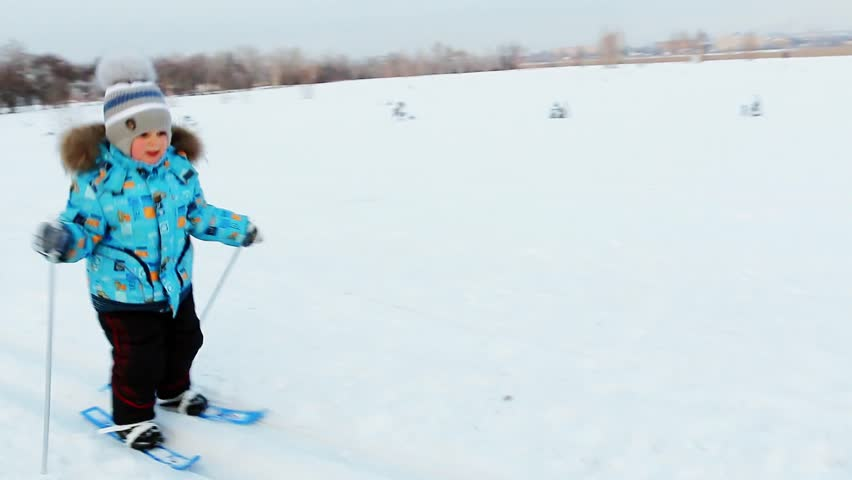 A little boy of three years learns to ski in the city Park in the evening | Shutterstock HD Video #1021213522