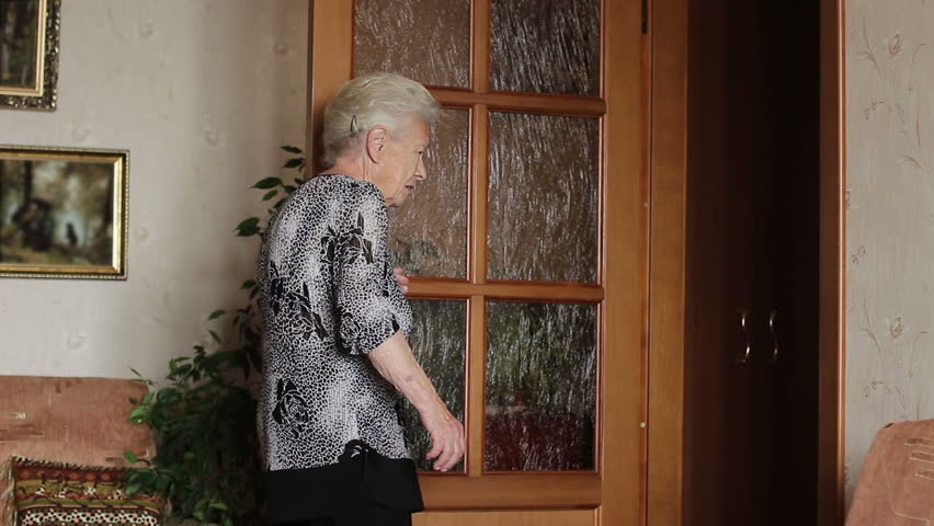 Old sick woman moves heavily around the apartment. Difficulty walking in old age #1021229662