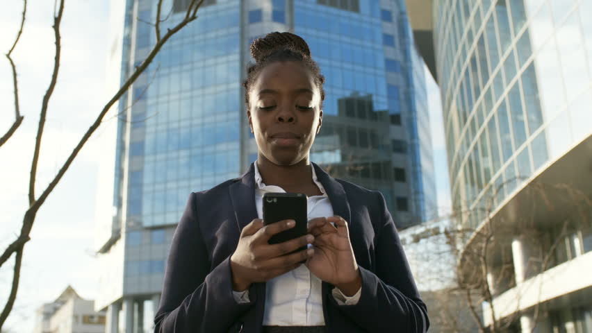 Low angle view of African businesswoman standing outdoors and using smartphone #1021267642