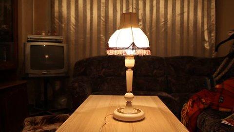 Vintage floor sensor lamp (made in USSR in 80s) in room of soviet flat. Man lights on  and lights off lamp