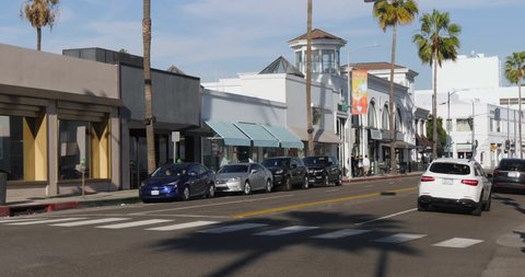 A daytime exterior establishing shot of traffic in the upscale shopping district near Rodeo Drive in Beverly Hills. Store names obscured for general stock use.