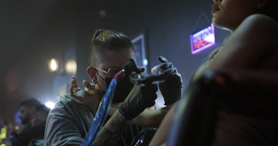 Young people in tattoo studio. Persons in beauty parlor and fashion salon for modern tattooing and body art. Man working as skilled professional artist and tattooist with experience at work | Shutterstock HD Video #1021296772