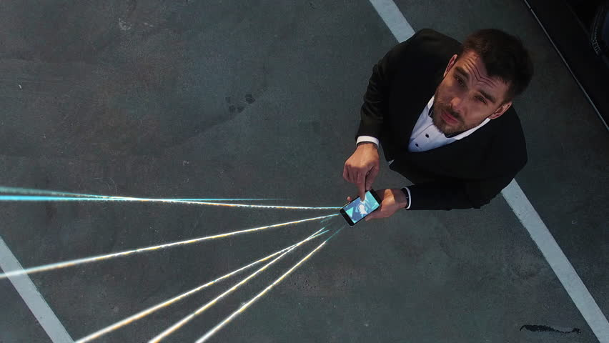 Big City Businessman Uses Smartphone, Stands on Skyscraper Roof: Visualization of Information Flows and Lines Flying from Mobile Phone into Global Network. Top Down Aerial Elevating Drone Shot. #1021307812